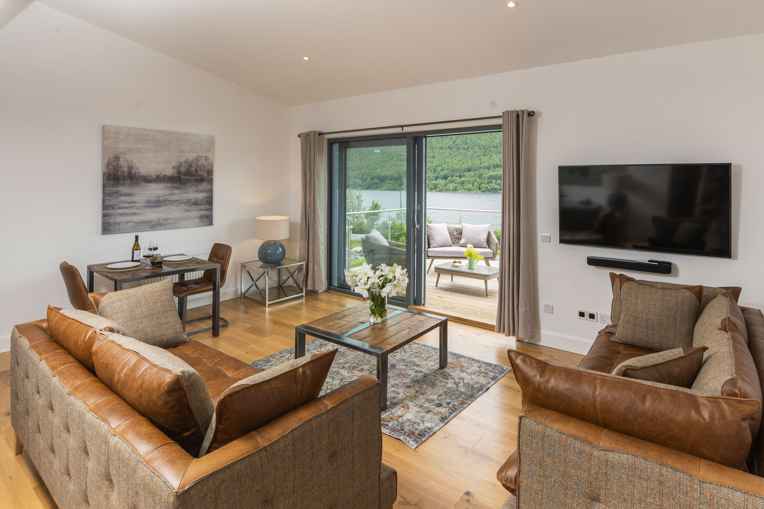 Open Plan Living Space With Brown Leather Sofas And View Of Loch