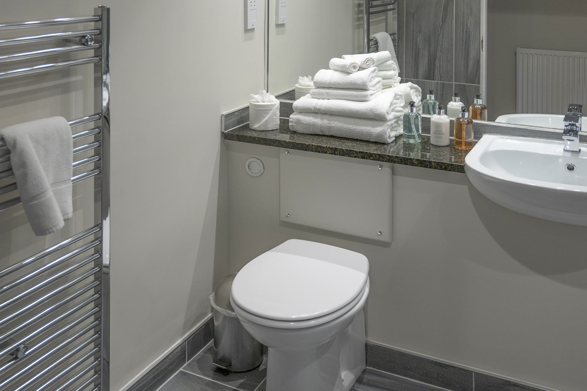 Modern White Wc And Basin With Chrome Radiator Reflected In Mirror With Towels And Soaps