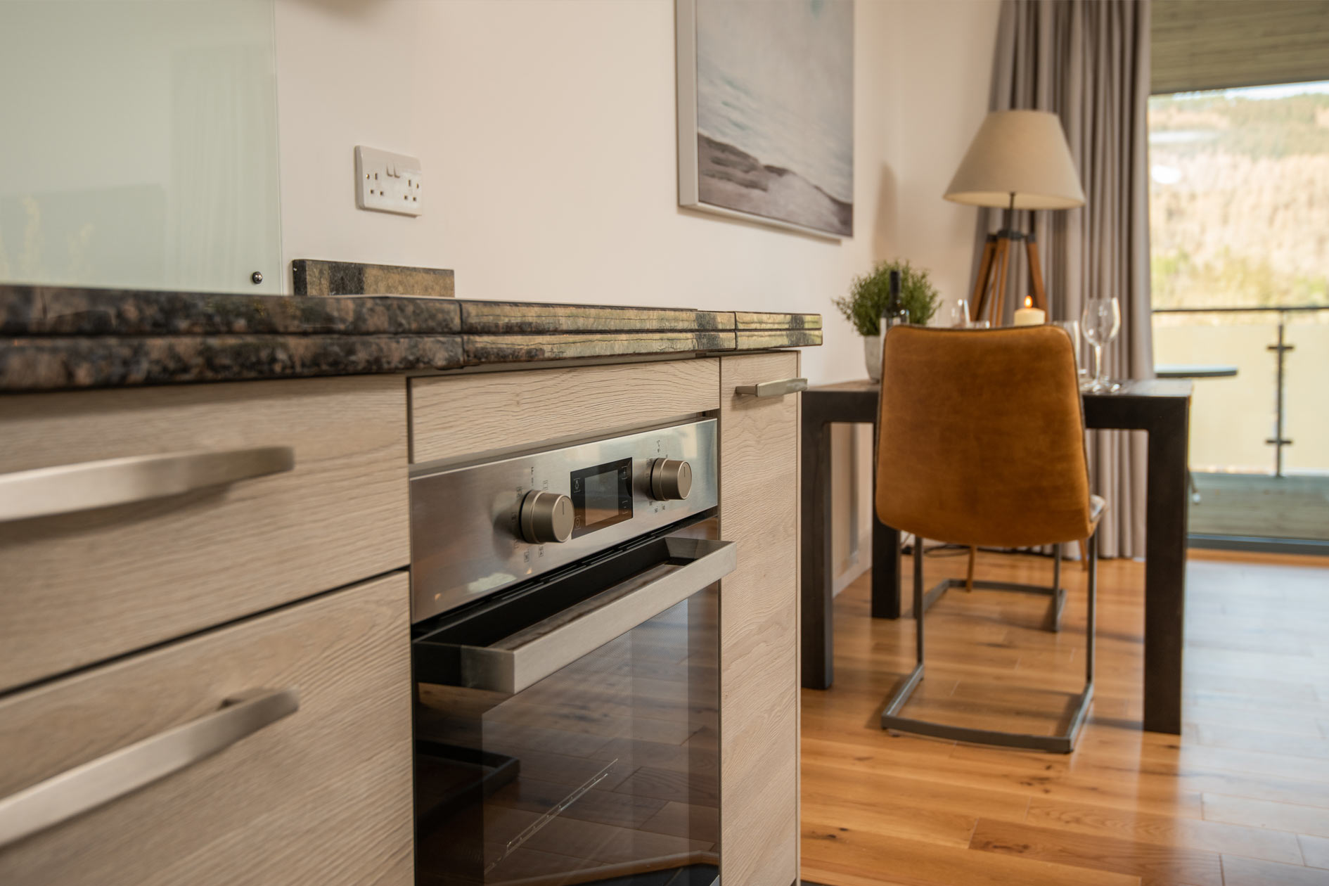 Close-up Of Kitchen Cupboards With Stainless Steel Oven And Leather Dining Chair With Lamp And Table Beyond