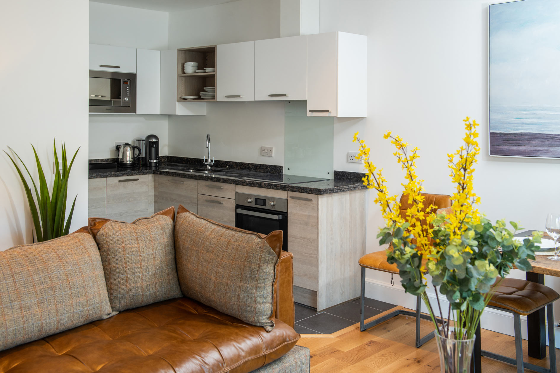 Open Living Space With Modern Kitchen And Brown Leather Sofa With Tweed Style Cushions And Vase Of Yellow Flowers
