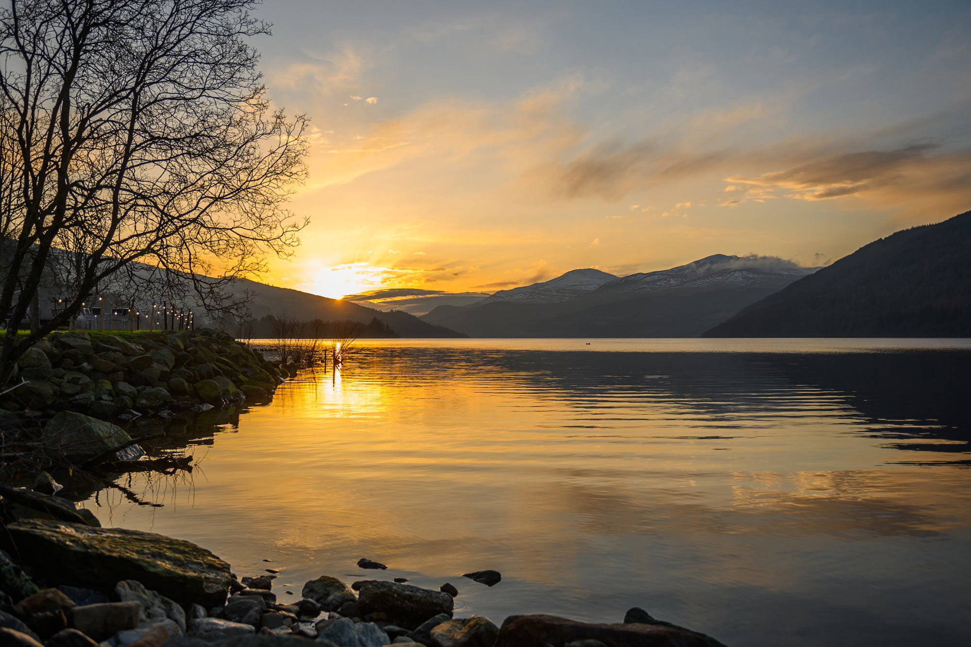 beautiful golden sunset reflected in loch tay rippling water surrounded by silhouetted hills