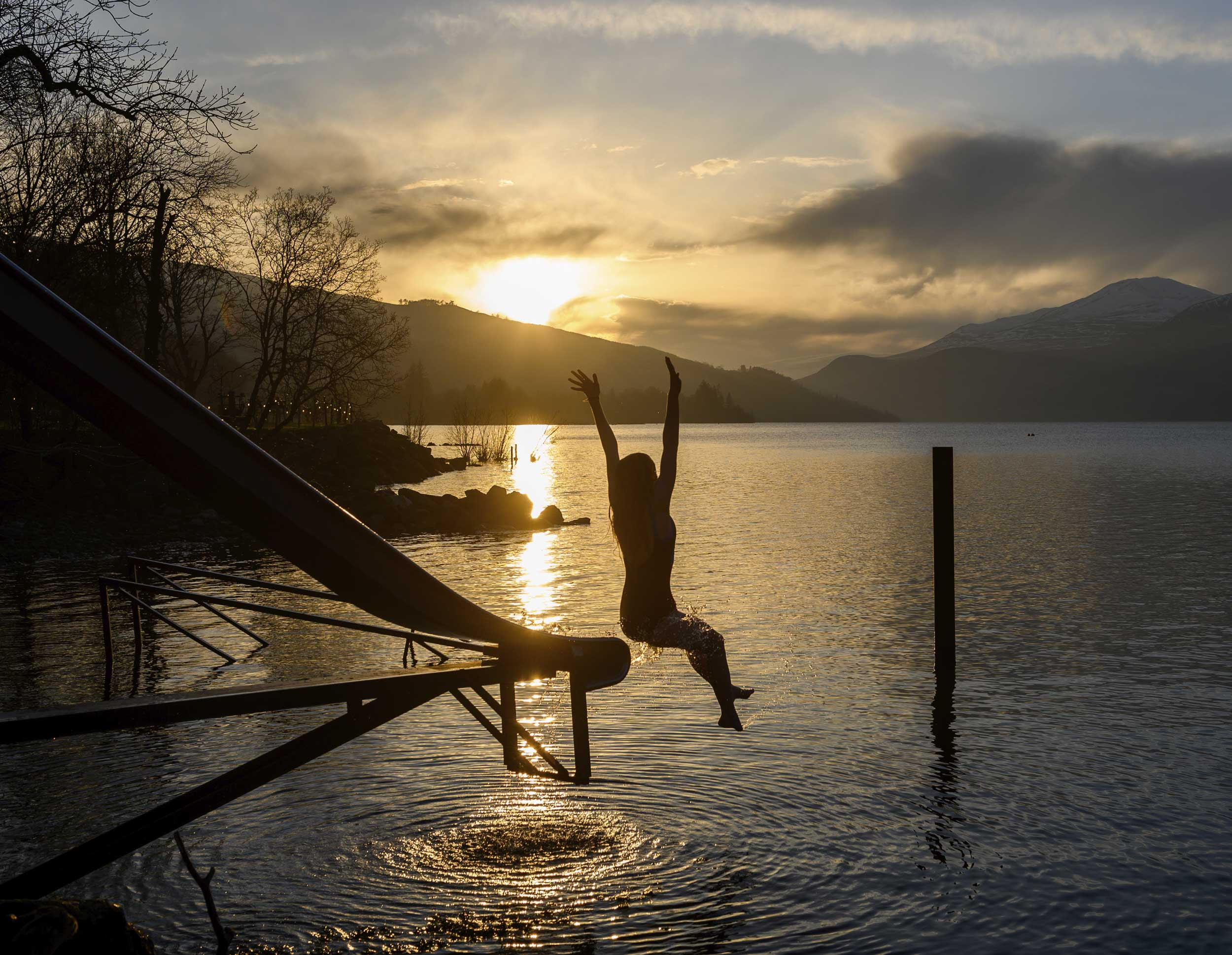 Silhouette Of Young Woman Jumping Off A Slide Into The Loch With A Golden Sunset And Mountain In Background