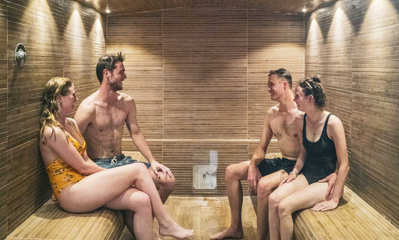 Four Young People In Bathing Suits Laughing And Talking As The Sit In Steam Room